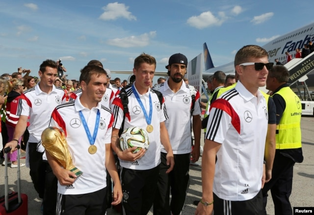 German soccer players Miroslav Klose, Philipp Lahm, Lars Bender, Sami Khedira and Toni Kroos (L-R) walk with the World Cup trophy at Tegel airport in Berlin, July 15, 2014.