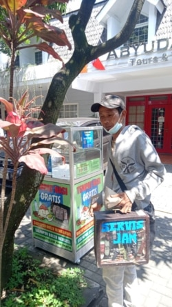 Seorang tukang perbaikan jam keliling sedang mengambil sebungkus nasi gratis. (Foto: Courtesy)