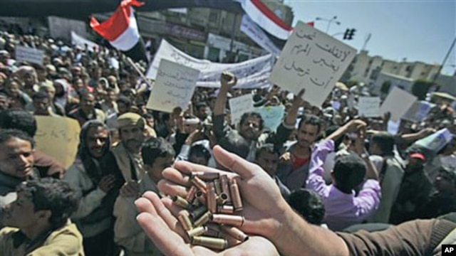 An anti-government protester displays bullet shells, claiming they were fired at demonstrators Tuesday night by Yemeni government supporters, killing at least one demonstrator, while demanding resignation of President Ali Abdullah Saleh, in Sanaa, Yemen,