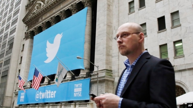 A man uses a mobile phone as he walks past the New York Stock Exchange ahead of Twitter IPO on November 7, 2013, in New York.