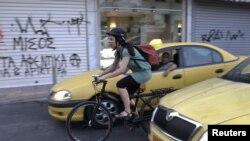 Warga Yunani, Elena Koniaraki, 39, mengendarai sepeda di antara taksi di pusat kota Athena. (Foto: Reuters/Yorgos Karahalis)