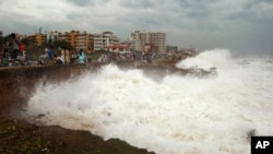 Indian people watch high tide waves as they stand at the Bay of Bengal coast in Vishakhapatnam, India, Oct. 12, 2013. Hundreds of thousands of people living along India's eastern coastline were taking shelter Saturday from a massive, powerful cyclone Phai
