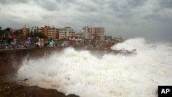 Warga menyaksikan ombak besar di pesisir Teluk Benggala di Vishakhapatnam, India (12/10).