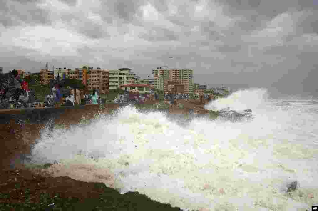 Indian people watch high tide waves as they stand at the Bay of Bengal coast in Vishakhapatnam. Hundreds of thousands of people living along the eastern coastline were taking shelter from a massive, powerful cyclone Phailin.