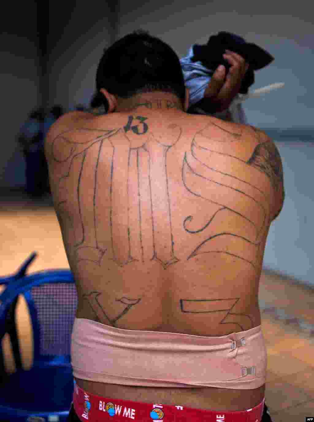 Un supposé membre du gang MS-13 couvre son visage lors d'une arrestation à San Salvador, le 31 janvier 2014.