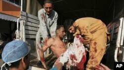 A man who is injured in a twin suicide bomb in Charsadda, is carried out from a vehicle after being brought to Lady Reading hospital in Peshawar, May 13, 2011