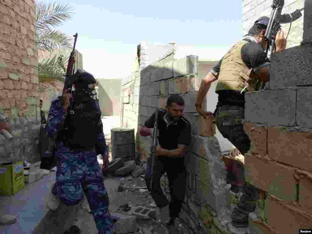 Members of Iraqi security forces and tribal fighters patrol the outskirts of the city looking for Islamic State militants, Ramadi, Sept. 14, 2014.