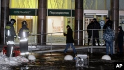 Police stand at the entrance of a supermarket, after an explosion in St. Petersburg, Russia, Dec. 27, 2017.