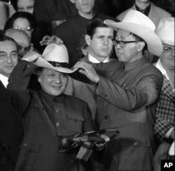 历史照片:在德克萨斯州西蒙顿的牛仔竞技场上,一名助手帮助中国国务院副总理邓小平试戴一顶牛仔帽。(1979年2月2日)