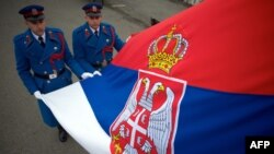 FILE - Serbian soldiers hold their country's flag in Belgrade.