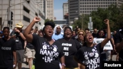 Activists raise their hands as they demand justice for the killing of Michael Brown while marching to the Thomas F. Eagleton United States Courthouse from City Hall in downtown St. Louis, Missouri, Aug. 26, 2014.