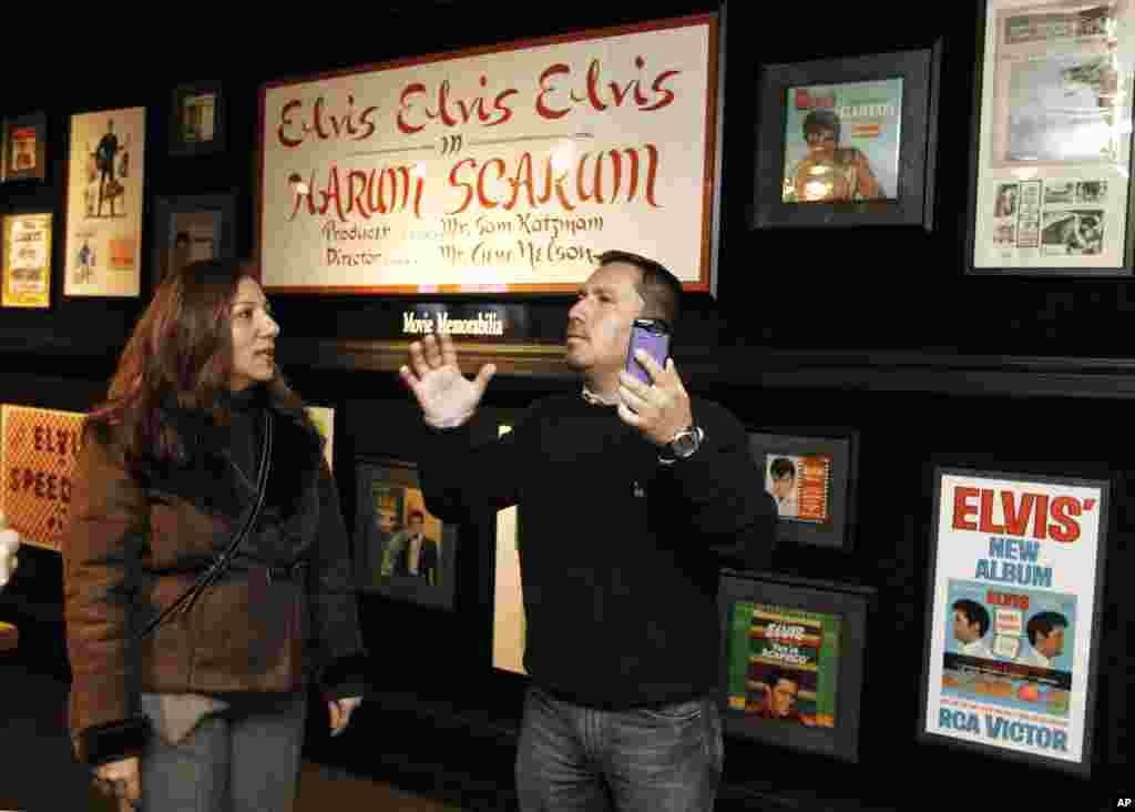 Edison Pena, right, and his translator, Lina Makarem, view some of Elvis Presley's movie memorabilia at Graceland, Elvis Presley's home, on Friday, Jan. 7, 2011, in Memphis, Tenn.