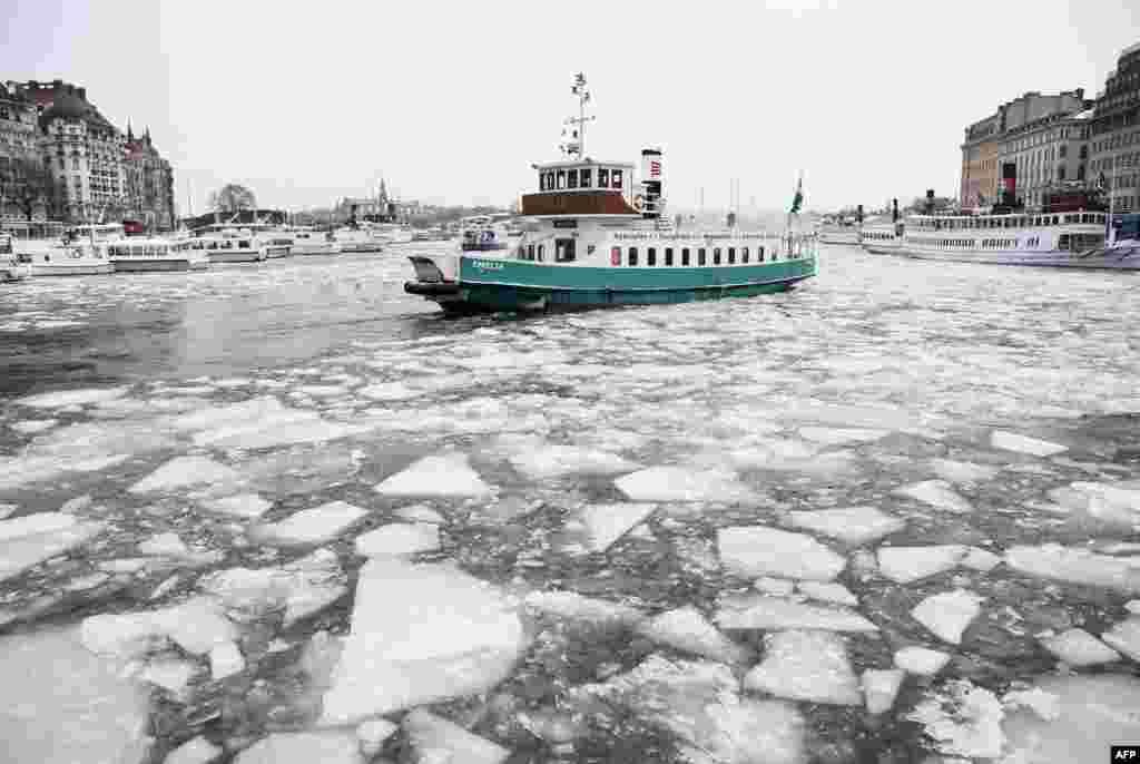 عبور یک قایق از آب یخ زده یک خلیج در استکهلم
