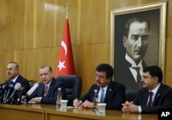 FILE - Turkish President Recep Tayyip Erdogan, second left, flanked by Foreign Minister Mevlut Cavusoglu, left, Economy Minister Nihat Zeybekci, second right, and Istanbul Gov. Vasip Sahin, speaks to reporters in Istanbul, Jan. 5, 2018. Erdogan slammed the conviction in New York of a Turkish banker accused of helping Iran evade sanctions, saying the U.S. justice system poses a danger for the world.