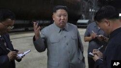 En esta imagen sin fecha, distribuida el 23 de julio de 2019 por el gobierno de Corea del Norte, el líder del país, Kim Jong Un (centro), habla mientras inspecciona un submarino recién construido en una localización no revelada de Corea del Norte.