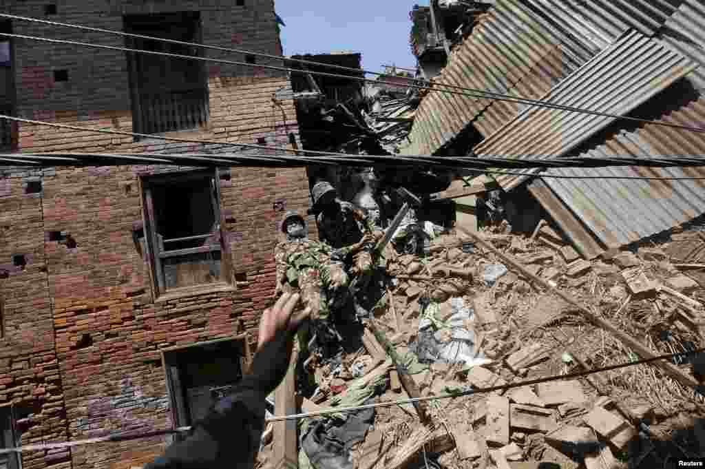A Nepalese army soldier loses his balance while descending from a mound of rubble during the recovery of a body from a house, in the aftermath of Saturday's earthquake in Bhaktapur, Nepal.