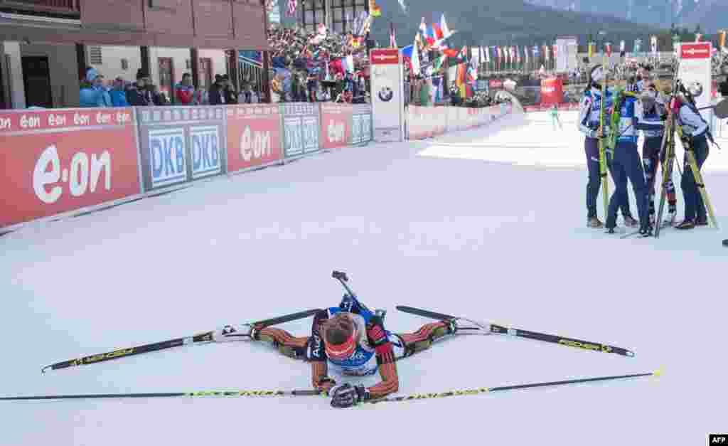 កីឡាការនីរបស់ក្រុមអ៊ីតាលី (រូបស្តាំ) រីករាយចំពោះជ័យជម្នះរបស់ពួកគេ នៅពេលដែលកីឡាការនី Franziska Preuss របស់ក្រុមអាល្លឺម៉ង់ដែលទទួលបានលេខពីរបានដេកនៅលើកន្លែងប្រកួត ក្នុងពេលការប្រកួតរត់របស់នារី ក្នុងព្រឹតិ្តការណ៍ IBU Biathlon World Cup ក្នុងក្រុង Hochfilzen ប្រទេសអូទ្រីស។