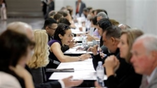 """People have their resumes reviewed at a job fair. Some experts say there is a """"skills gap"""" between jobseekers and jobs. Some researchers however say evidence of a skills gap is weak."""