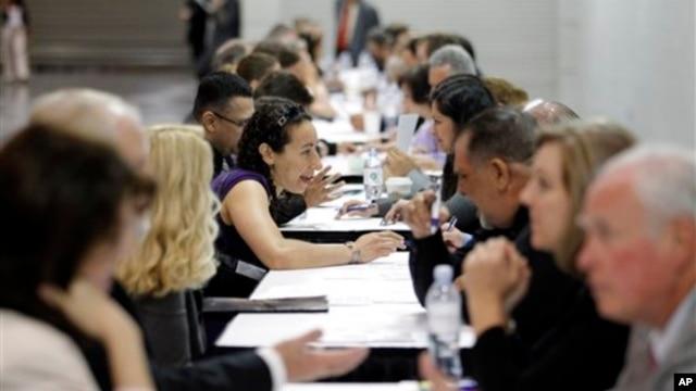 Người tìm việc nộp hồ sơ cho các nhà tuyển dụng trong một hội chợ việc làm ở bang California, Mỹ.