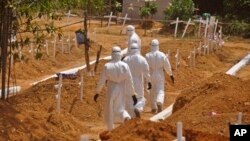 FILE - Health workers walk inside a new graveyard as they move bury people suspected of dying from the Ebola virus on the outskirts of Monrovia, Liberia, March 11, 2015.