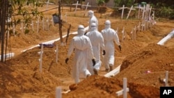 Health workers walk inside a new graveyard as they move bury people suspected of dying from the Ebola virus on the outskirts of Monrovia, Liberia, Wednesday, March 11, 2015. Liberians held a church service Wednesday for families who lost members to Ebola to mark the country's 99th celebration National Decoration Day, a holiday normally set aside for people to clean up and re-decorate the graves of their lost relatives. (AP Photo/Abbas Dulleh)