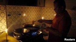 Một người đàn ông nấu ăn gần những cây nến tại nhà khi bị cắt điện ở San Cristobal, bang Tachira, Venezuela, ngày 25 tháng 4 năm 2016.