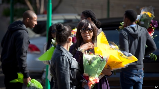 Granddaughter Ndileka Mandela, center, gestures as she and other family relatives carry bunches of flowers that were left by wellwishers into the Mediclinic Heart Hospital, June 27, 2013.