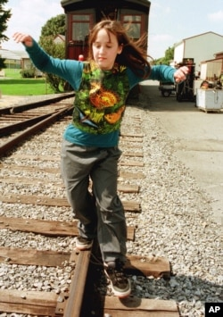 "Actress Mara Wilson balances herself as she walks the rails as she relaxes during a lunck break in the filming of ""Thomas and the Magic Railroad"" in Strasburg, Pennsylvania, Sept. 13, 1999."
