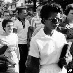 1957年9月4日,黑人女学生伊丽莎白.埃克福德和在后面跟随她的愤怒的人群