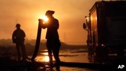 Dos bomberos enrrollan sus mangueras luego de combatir un incendio en Carlsbad, California.
