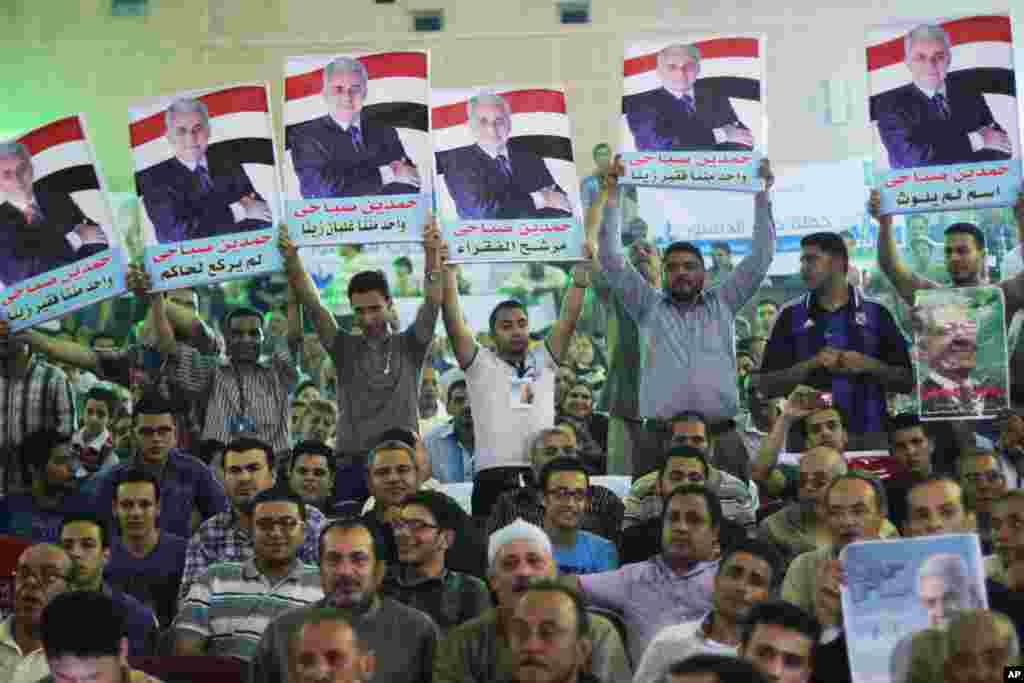 Supporters of presidential candidate Hamdeen Sabahi raise posters of him during his campaign in Mahalla, 125 kilometers north of Cairo, May 5, 2014.