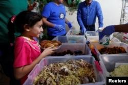 """Seorang anak perempuan menerima makanan dari """"Dapur Keluarga"""" yang mengemas makanan berlebih dari hotel bintang lima dan membagikan kepada masyarakat miskin selama Ramadan, di kamp Palestina Al-Baqaa, dekat Amman, Yordania, 11 Juni 2018."""