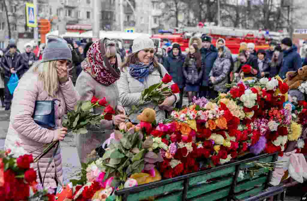 People lay flowers for the victims of a fire in a multi-story shopping center in the Siberian city of Kemerovo, about 3,000 kilometers (1,900 miles) east of Moscow, Russia.