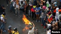 Demonstran membakar barikade saat bentrok dengan petugas keamanan sementara pemilu sedang berlangsung di Caracas, Venezuela, 30 Juli 2017.