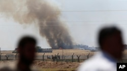 In this photo taken from the Turkish side of the border between Turkey and Syria, in Akcakale, southeastern Turkey, people watch as smoke from a U.S.-led airstrike rises over the outskirts of Tal Abyad, Syria, June 15, 2015.