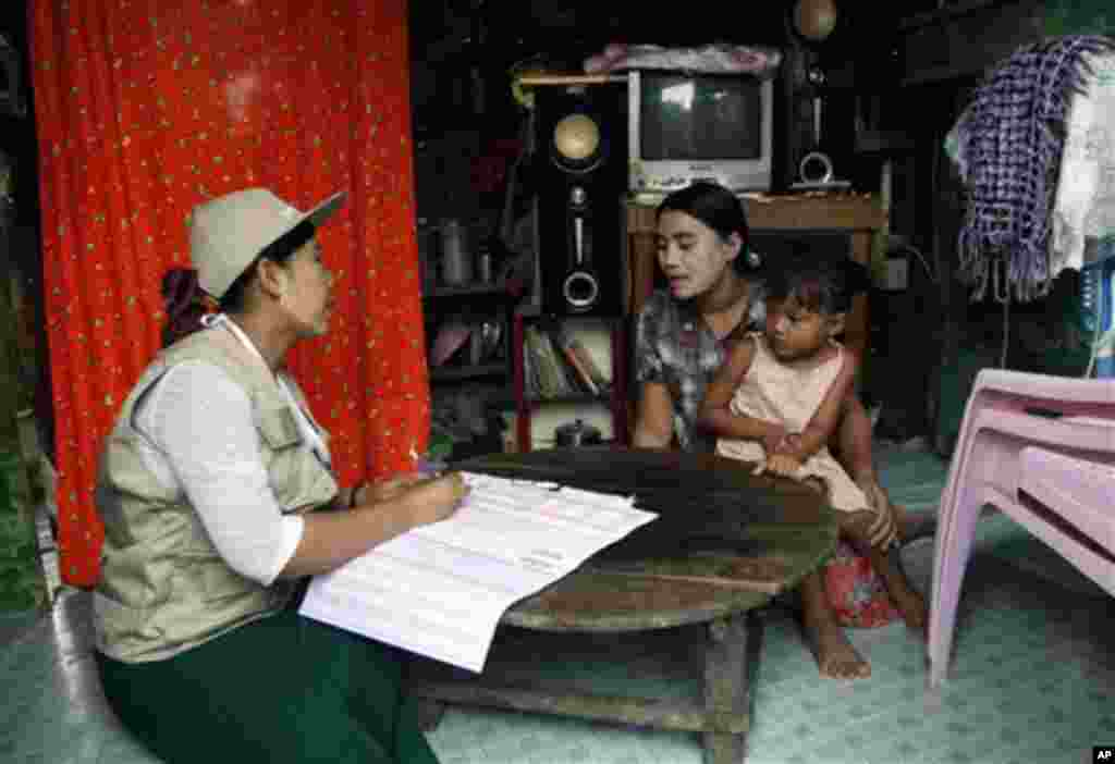 A Myanmar census enumerator asks questions to a housewife while collecting information in Dala township Sunday, March 30, 2014, in Yangon, Myanmar. Enumerators fanned out across Myanmar on Sunday for a census that has been widely criticized for stoking r