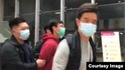 香港中文大學校園電台報道,警方1月底進入校園就黑衣人向保安員撒粉事件採取搜捕行動,在學生宿舍拘捕一名學生(紅衣者),是中大學生會前會長區倬僖。(中大校園電台直播截圖)
