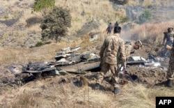 پاکستانی فوجی بھارتی فضایہ کے جنگی طیارے کے ملبے کے گرد جمع ہیں