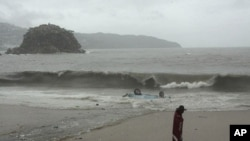 A person walks past an upturned car by the shore after the vehicle was swept into the ocean by high waves caused by the approach of Tropical Storm Beatriz in Acapulco, June 20, 2011