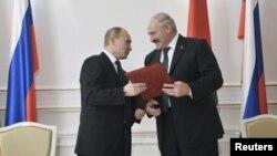 Presiden Belarus Alexander Lukashenko (kanan) dan Presiden Rusia Vladimir Putin dalam penandatanganan kerjasama di Minsk (31/5). Putin menjanjikan dukungan moral dan pinjaman dana bagi Belarus.