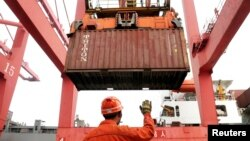 FILE PHOTO: An employee guides as a crane unloads shipping containers from a cargo ship at a port in Lianyungang, Jiangsu province, China, March 8, 2014.