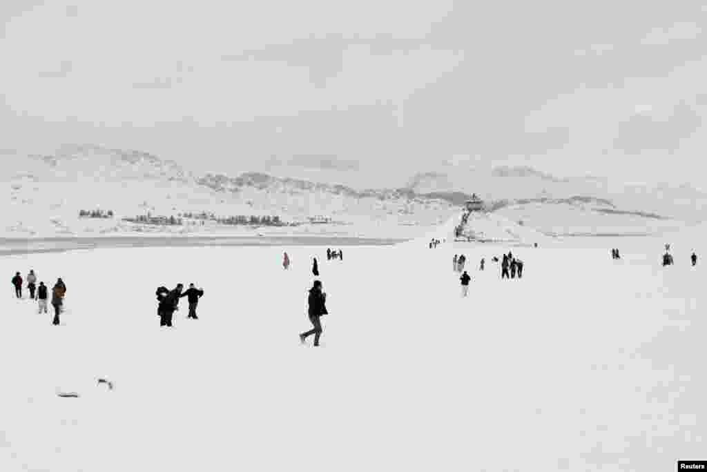 People visit the Hanna Lake after a snowfall on the outskirts of Quetta, Pakistan.