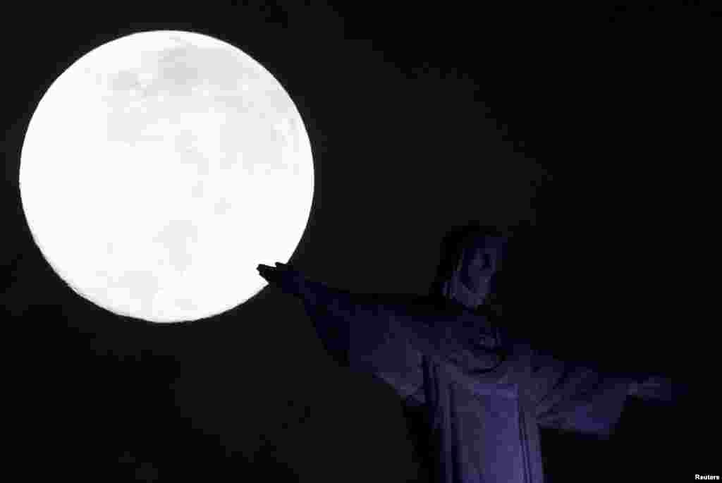 """2018年2月1日,在巴西里约热内卢的基督救世主雕像旁边的""""超级月亮""""。这让人想起李白的乐府诗:""""小时不识月, 呼作白玉盘。又疑瑶台镜, 飞在青云端。 """""""