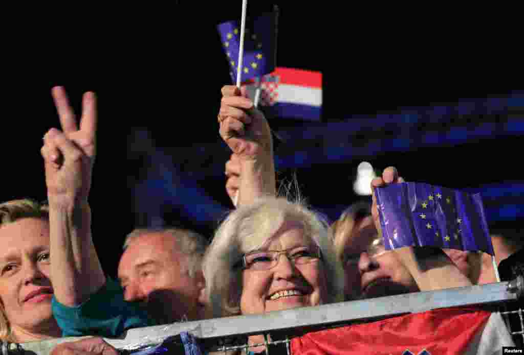 A woman makes victory sign as she holds the EU flag during the celebration of the accession of Croatia to the European Union in Zagreb, June 30, 2013.