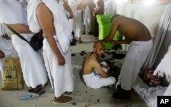 Peregrinos musulmanes hacen fila mientras esperan afeitarse la cabeza de forma gratuita después de arrojar piedras a un pilar que simboliza la lapidación de Satanás, en el primer día de Eid al-Adha, al final de la peregrinación anual del haj. Agosto 11 de 2019. AP foto.