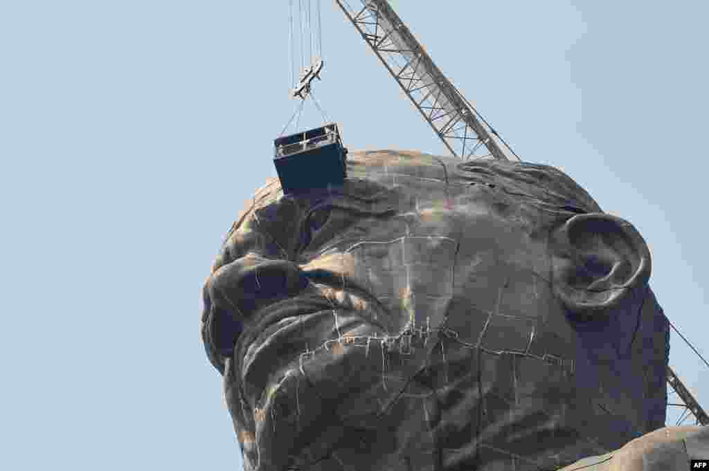 Indian workers give the finishing touches to the world's tallest statue dedicated to Indian independence leader Sardar Vallabhbhai Patel. The statue overlooks the Sardar Sarovar Dam near Vadodara, in India's western Gujarat state.