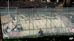 A man walks past the smoldering remains of burnt out buildings at Sydney's Villawood Detention Centre, April 21, 2011