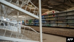 A picture shows empty shelves, including those for bread, in a groceries store in Harare on October 9, 2018, as Zimbabwe is experiencing renewed shortages. - In one of the biggest supermarkets in Harare, Zimbabwe's capital, cooking oil, rice and Coca-Cola are all out of stock while a notice on the bread rack tells shoppers they can only buy one loaf each. (Photo by Jekesai NJIKIZANA / AFP)