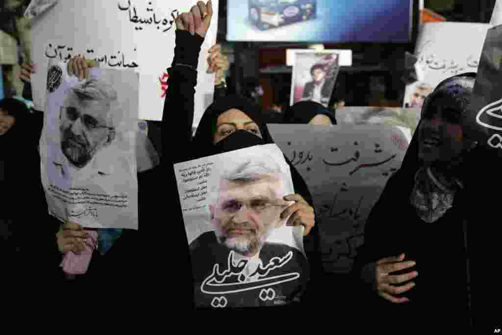 Supporters of the Iranian presidential candidate Saeed Jalili, shown in the posters, chant slogans, Tehran, Iran, June 9, 2013.