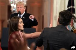 As President Donald Trump points to CNN's Jim Acosta, a White House aide tries to take the microphone from him during a news conference in the East Room of the White House, Nov. 7, 2018, in Washington.